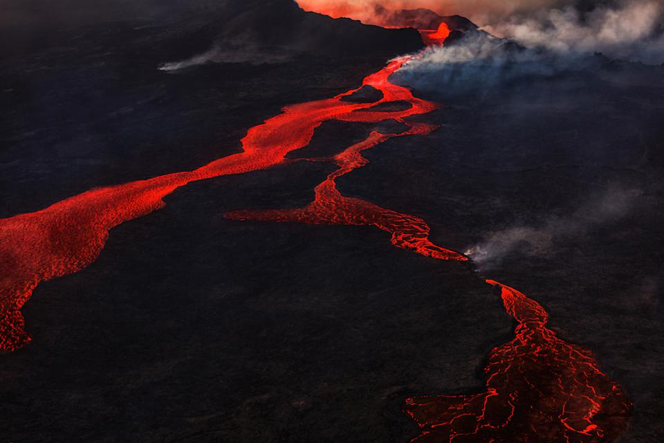 Lava and plumes from the Holuhraun Fissure Eruption by the Bardarbunga Volcano, Iceland. On August 29, 2014, a fissure eruption started in Holuhraun at the northern end of a magma intrusion that had moved progressively north, from the Bardarbunga volcano. Bardarbunga is a stratovolcano located under Vatnajokull, Iceland's most extensive glacier.
