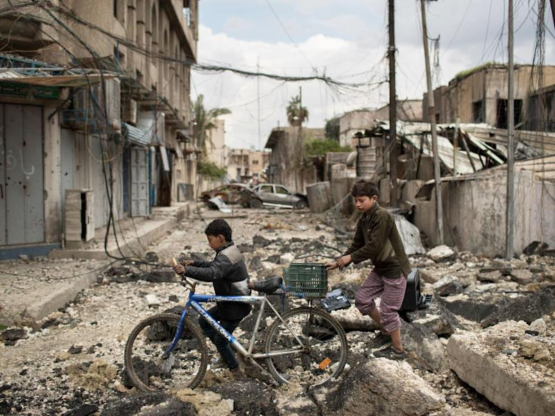 Iraqi boys cross a destroyed street in a western Mosul neighbourhood recently retaken by Iraqi security forces (AP)