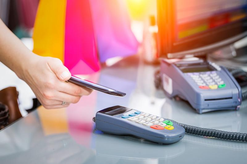 Shopper paying at store with mobile payment feature on smartphone.