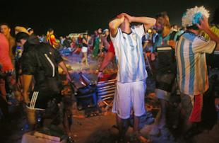 An Argentina fans mourn his team's loss to Germany on Copacabana Beach. (Getty)