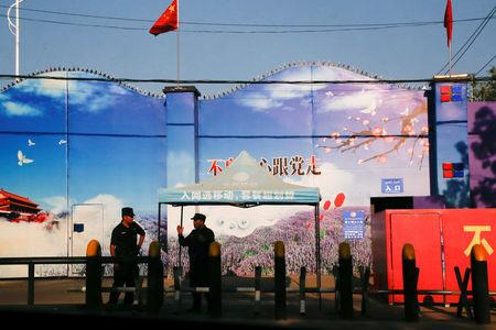 FILE PHOTO: Security guards stand at the gates of what is officially known as a vocational skills education centre in Huocheng County in Xinjiang Uighur Autonomous Region, China September 3, 2018. REUTERS/Thomas Peter/File Photo