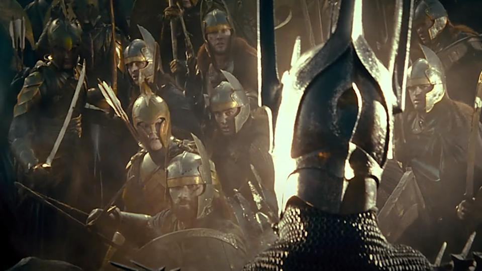 Sauron dressed in armor looks out at a group of soldiers in a scene from The Lord of the Rings: The Fellowship of the Ring.