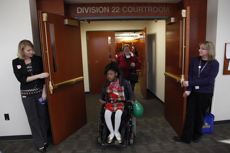 In this Nov. 14, 2012 photo, Adrianne, 13, the disabled adopted daughter of Carrie Ann Lucas, exits a court where a judge finalized the adoption for one of her siblings at the Arapahoe County Justice Center in Centennial, Colo., on National Adoption Day. Carrie Ann Lucas says the prejudice she encountered prompted her to go to law school, to better defend her own rights and those of other disabled parents. (AP Photo/Brennan Linsley)