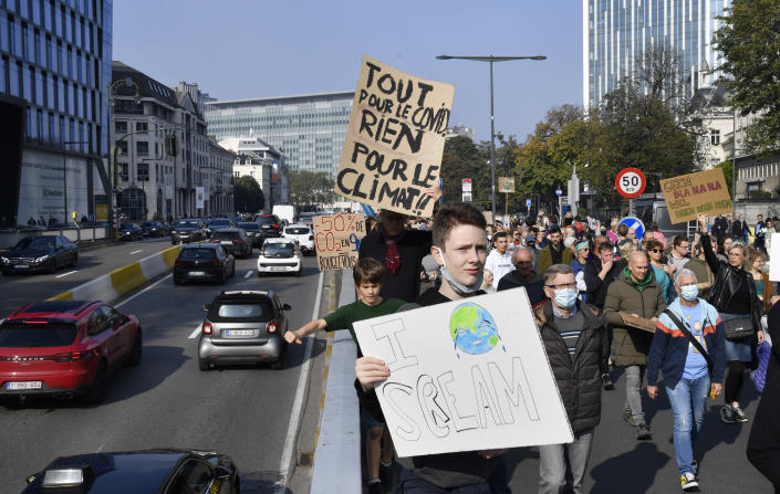 People hold signs and banners as they participate in a climate march and demonstration in Brussels, Sunday, Oct. 10, 2021. Some 80 organizations are joining in a climate march through Brussels to demand change and push politicians to effective action in Glasgow later this month. Sign at left reads in French: 'Everything for COVID, nothing for climate'. (AP Photo/Geert Vanden Wijngaert)