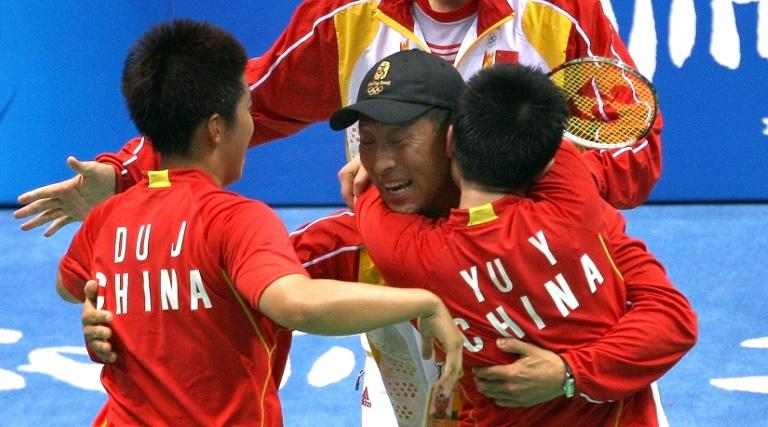China's badminton duo Du Jing (L) and Yu Yang celebrate with head coach Li Yongbo after their gold-medal victory at the 2008 Beijing Olympic Games