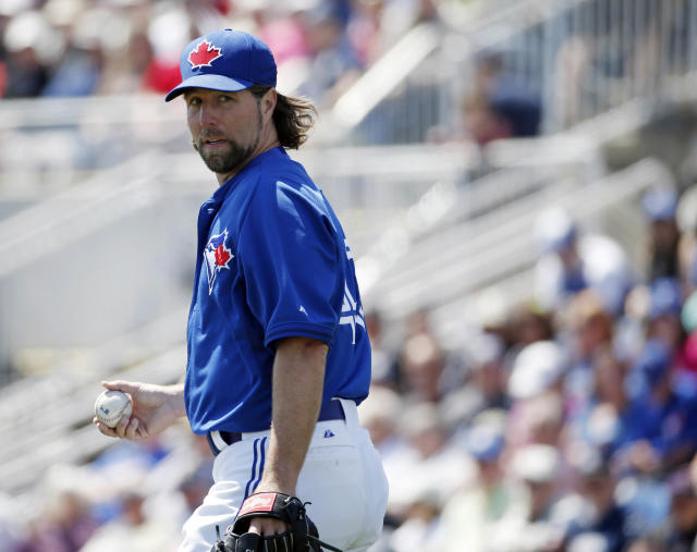 Toronto Blue Jays starting pitcher R.A. Dickey looks over his shoulder in a spring training baseball game against the New York Yankees in Dunedin, Fla., Wednesday, March 26, 2014. (AP Photo/Kathy Willens)