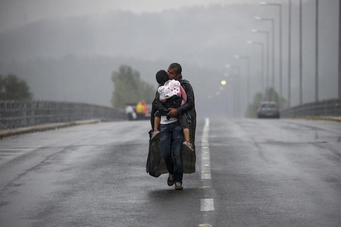 <p>A Syrian refugee kisses his daughter as he walks through a rainstorm toward Greece's border with Macedonia, near the Greek village of Idomeni, Sept. 10, 2015. <i>(Yannis Behrakis/Reuters)</i></p>