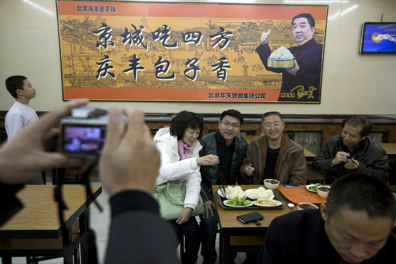 "Tourists from Guangdong province, who ordered similar food to what Chinese President Xi Jinping ate the day before, pose for photos at the Qing-Feng Steamed Dumpling Shop in Beijing, China, Sunday, Dec. 29, 2013. Xi dropped in unexpectedly Saturday at the traditional Beijing bun shop, where he queued up, ordered and paid for a simple lunch of buns stuffed with pork and onions, green vegetables, and stewed pig livers and intestines. The sign in the background is an advertisement for the restaurant which reads ""Capital city food from all places, Qing-Feng buns are fragrant."" (AP Photo/Ng Han Guan)"