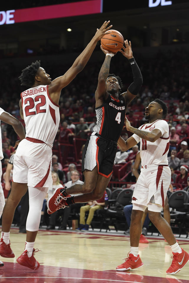 Georgia guard Tyree Crump (4) drives to the hoop past Arkansas defenders Gabe Osabuohien (22) and Keyshawn Embery-Simpson (11) during the second half of an NCAA college basketball game, Tuesday, Jan.29, 2019 in Fayetteville, Ark. (AP Photo/Michael Woods)
