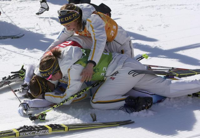 Sweden's Charlotte Kalla lies on the ground after crossing the finish line as her team-mates Emma Wiken (C), Anna Haag (top) and Ida Ingemarsdotter (rear) celebrate their first place in the women's relay 4x5km cross-country event at the Sochi 2014 Winter Olympic Games in Rosa Khutor February 15, 2014. REUTERS/Sergei Karpukhin (RUSSIA - Tags: SPORT SKIING OLYMPICS)