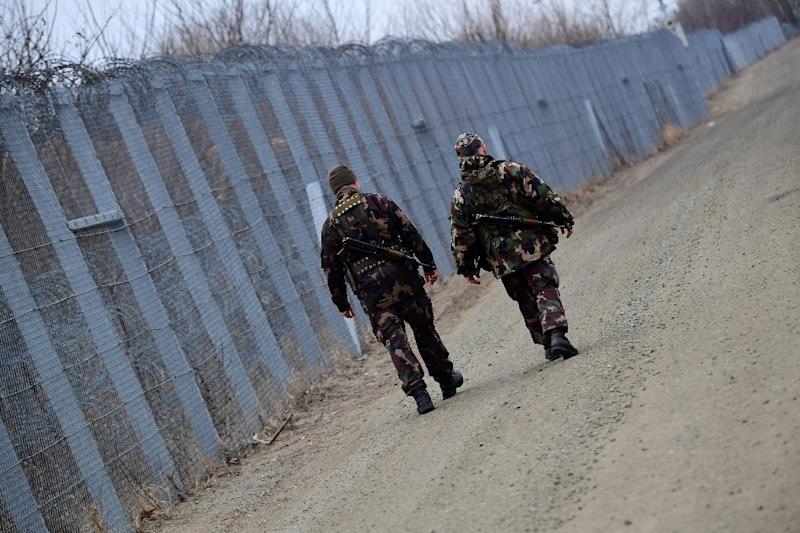 Soldiers patrol along the border fence on the Hungarian-Serbian border in February 2017