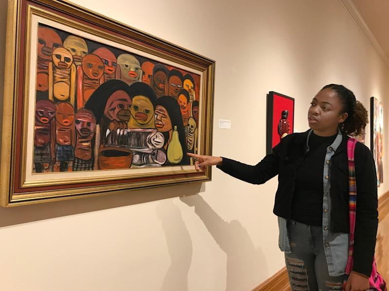 """Norfolk State University fine arts senior D'Shea Downey points to her favorite piece of art from the exhibit, """"A Taste for the Beautiful: African Impact on American Culture,"""" at Hampton University Museum in Hampton, Virginia, on Friday, Nov. 22, 2019."""