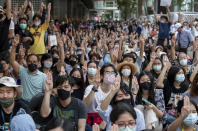 Pro-democracy protesters flash three-fingered salute during a protest march in the central business district in Bangkok, Thailand, Thursday, Oct. 15, 2020. Thailand's government declared a strict new state of emergency for the capital on Thursday, a day after a student-led protest against the country's traditional establishment saw an extraordinary moment in which demonstrators heckled a royal motorcade. (AP Photo/ Gemunu Amarasinghe)