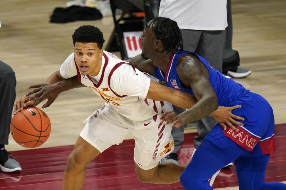 Kansas guard Marcus Garrett, right, tries to steal the ball from Iowa State guard Rasir Bolton during the second half of an NCAA college basketball game, Saturday, Feb. 13, 2021, in Ames, Iowa. Kansas won 64-50. (AP Photo/Charlie Neibergall)