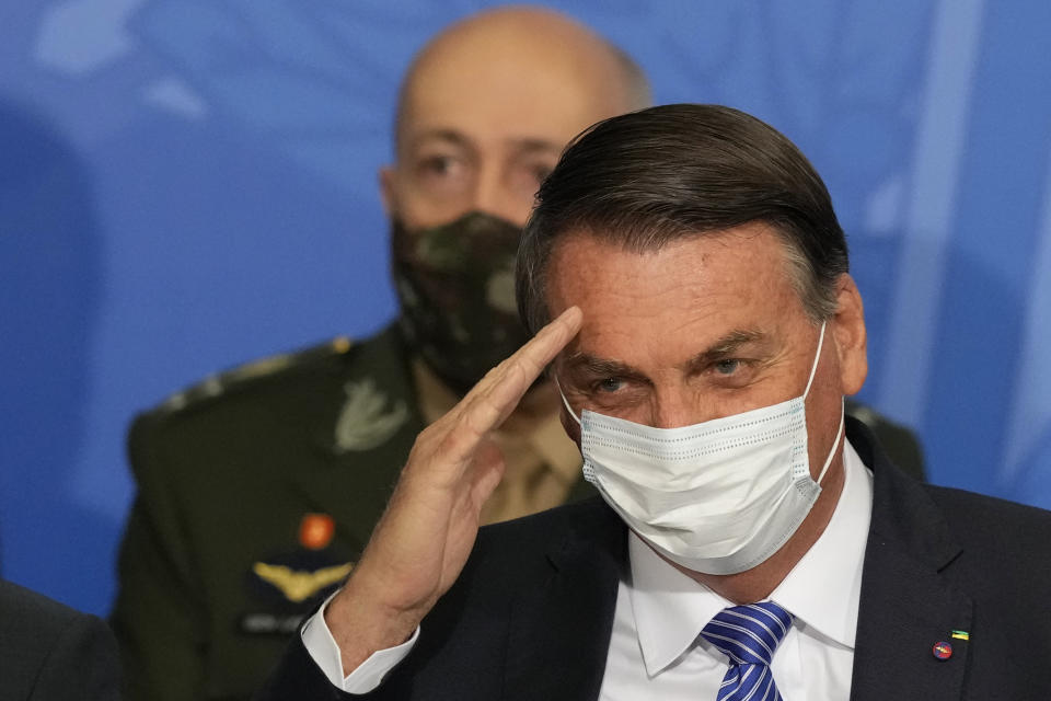 Brazil's President Jair Bolsonaro salutes, as Army Commander Paulo Sergio Nogueira de Oliveira stands behind him during a swearing-in ceremony at the Planalto presidential palace, in Brasilia, Brazil, Wednesday, Aug. 4, 2021. (AP Photo/Eraldo Peres)