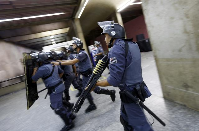 Policemen in riot gear walk inside Ana Rosa subway station during the fifth day of metro worker's protest in Sao Paulo June 9, 2014. A court set a 500,000 reais penalty ($223,000) for each day they stay off work from Monday and also declared the strike illegal, complicating preparations for the World Cup opening match. REUTERS/Kai Pfaffenbach (BRAZIL - Tags: BUSINESS EMPLOYMENT SOCCER SPORT TRANSPORT CIVIL UNREST WORLD CUP)