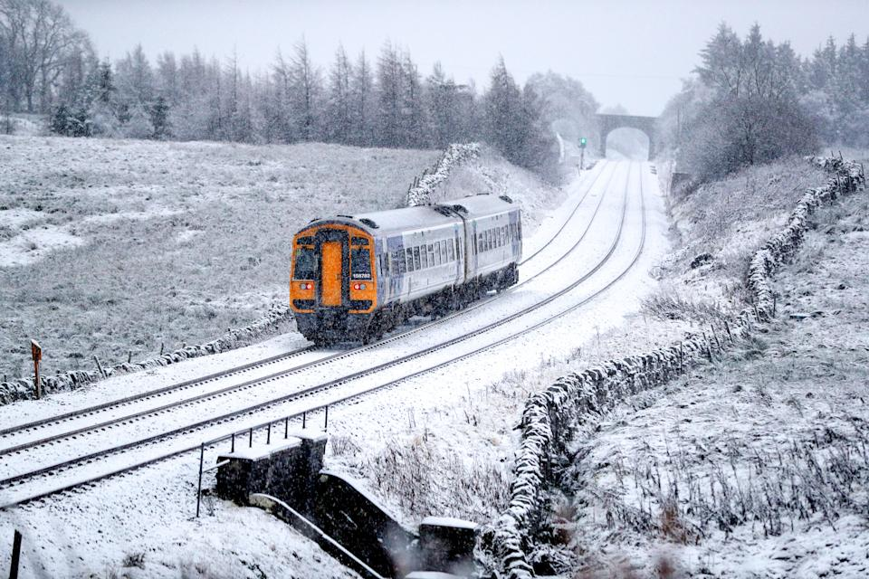 A train runs along the tracks in snowy North Yorkshire with the UK expecting more wintry weather ahead of the first weekend of December, with warnings in place for ice and snow.
