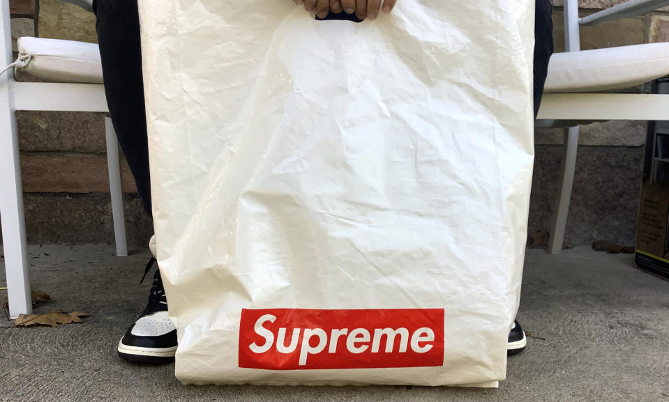 The Supreme logo appears on a plastic shopping bag in Fort Lee, N.J., Monday, Nov. 9, 2020. VF Corp., the owner of The North Face, Vans and Timberland brands, is buying privately held streetwear company Supreme as it looks to grow its online and direct-to-consumer business. (AP Photo/Pablo Salinas)
