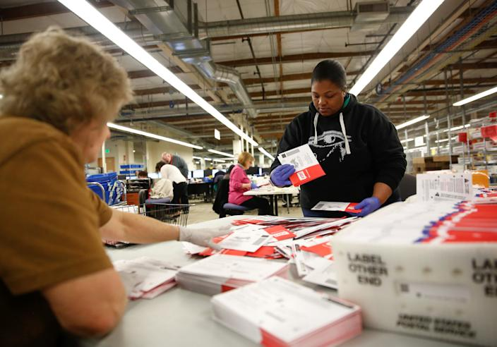 Workers prepare ballots from a drop box for a mail sorting machine