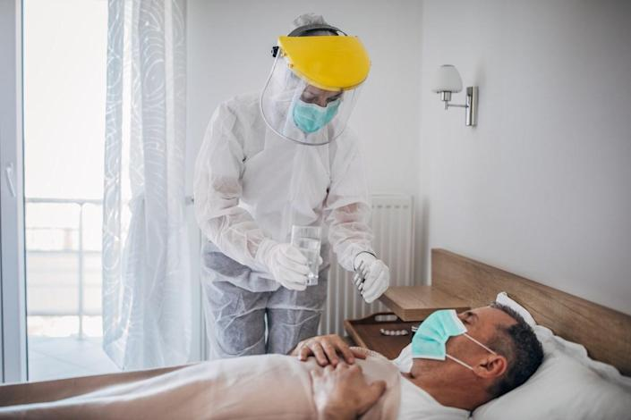 Doctor giving medicine to a man lying in hospital bed because of coronavirus infection