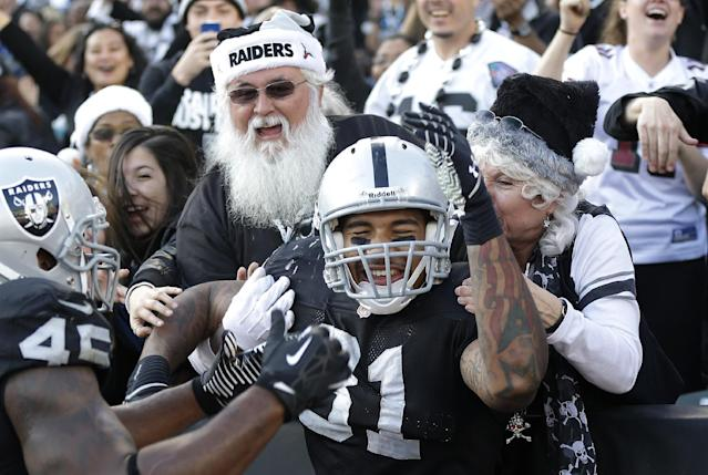Oakland Raiders tight end Mychal Rivera (81) celebrates with fullback Marcel Reece (45) and fans after catching a 14-yard touchdown from quarterback Matt McGloin against the Kansas City Chiefs during the third quarter of an NFL football game in Oakland, Calif., Sunday, Dec. 15, 2013. (AP Photo/Marcio Jose Sanchez)