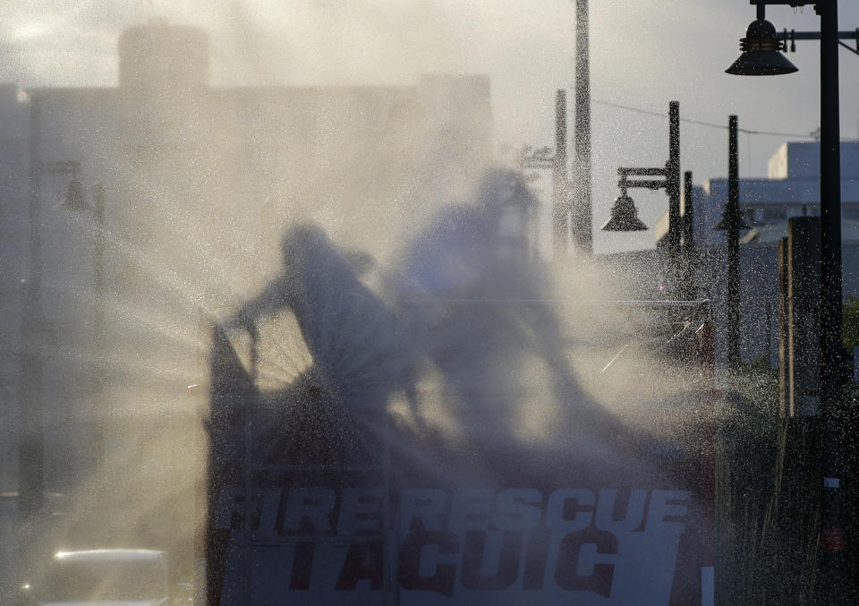 Firemen spray disinfectants along a street during a continuing enhanced community quarantine to prevent the spread of the new coronavirus in Taguig, Metro Manila, Philippines, Wednesday, April 29, 2020. (AP Photo/Aaron Favila)