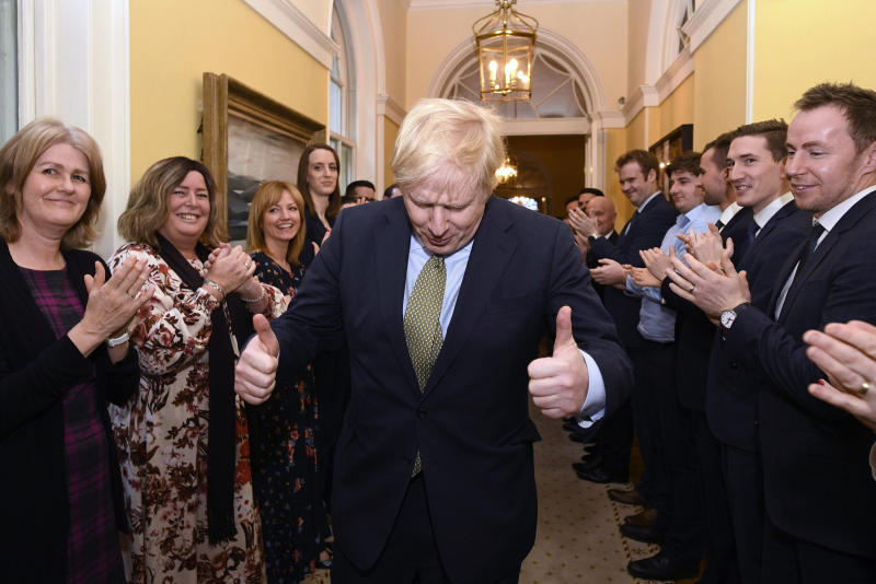 Britain's Prime Minister Boris Johnson is greeted by staff as he returns to 10 Downing Street, London, after meeting Queen Elizabeth II at Buckingham Palace and accepting her invitation to form a new government, Friday Dec. 13, 2019.  Boris Johnson led his Conservative Party to a landslide victory in Britain's election that was dominated by Brexit. (Stefan Rousseau/PA via AP)