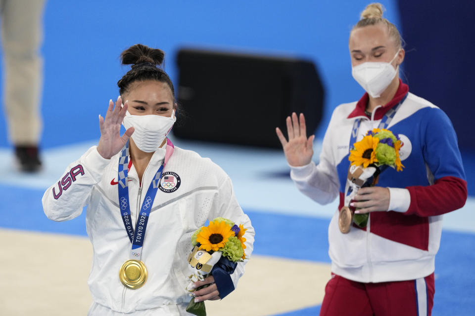 Gold medallist Sunisa Lee of the Unites States, left, and bronze medallist Angelina Melnikova, of the Russian Olympic Committee, celebrate during the medal ceremony for the artistic gymnastics women's all-around at the 2020 Summer Olympics, Thursday, July 29, 2021, in Tokyo. (AP Photo/Ashley Landis)
