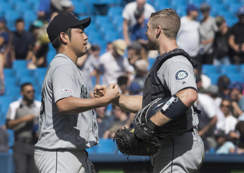 Seattle Mariners starting pitcher Yusei Kikuchi shakes hands with catcher Tom Murphy after pitching a complete game shutout against the Toronto Blue Jays in a baseball game in Toronto, Sunday, Aug. 18, 2019. (Fred Thornhill/The Canadian Press via AP)