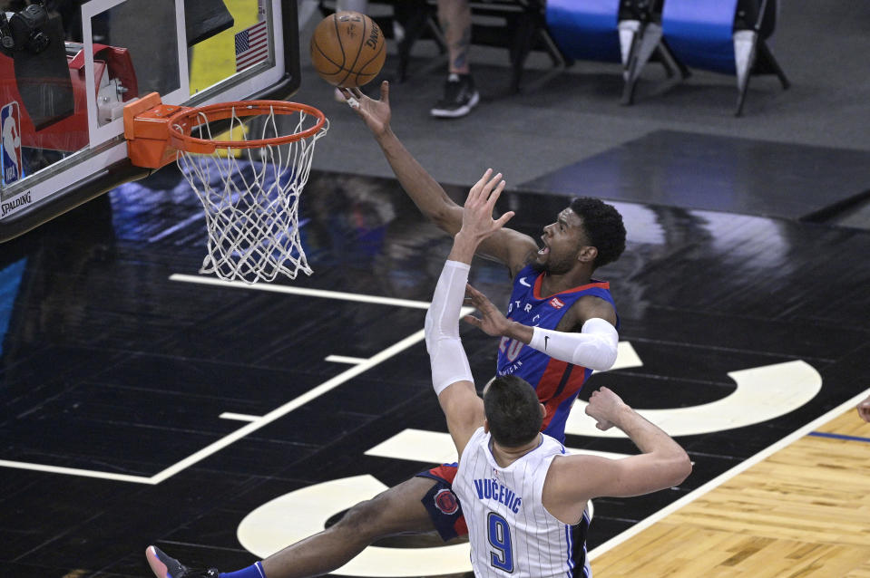 Detroit Pistons guard Josh Jackson (20) goes up for a shot in front of Orlando Magic center Nikola Vucevic (9) during the second half of an NBA basketball game, Tuesday, Feb. 23, 2021, in Orlando, Fla. (AP Photo/Phelan M. Ebenhack)