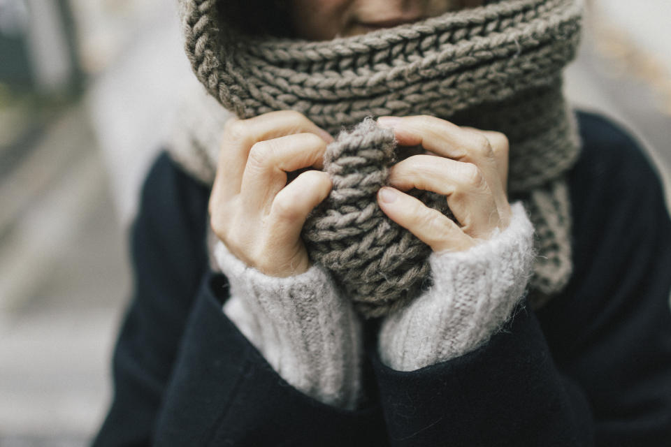 Woman's hand holding knitted scarf, close-up