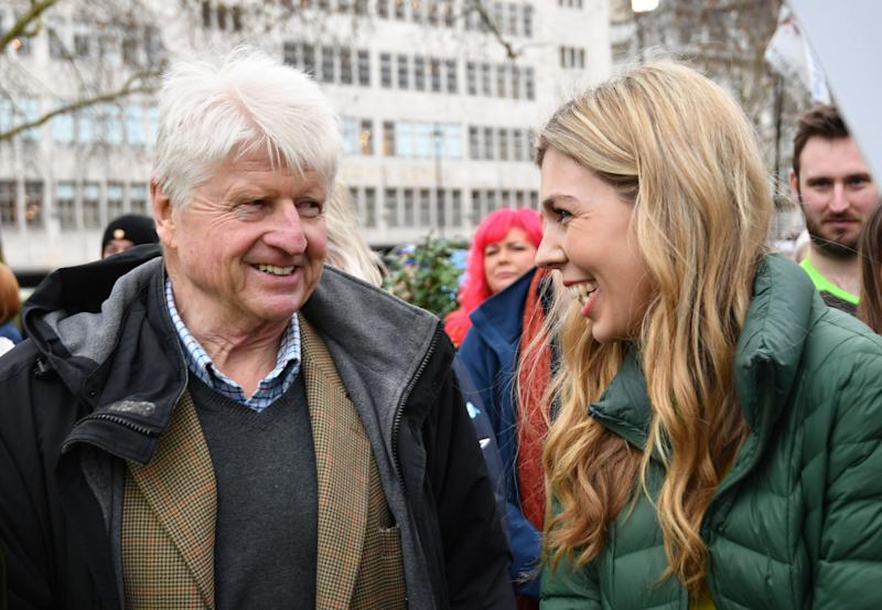 Mr Johnson's partner, Carrie Symonds, with his father, Stanley, at an anti-whaling protest in London (Picture: PA/Getty)