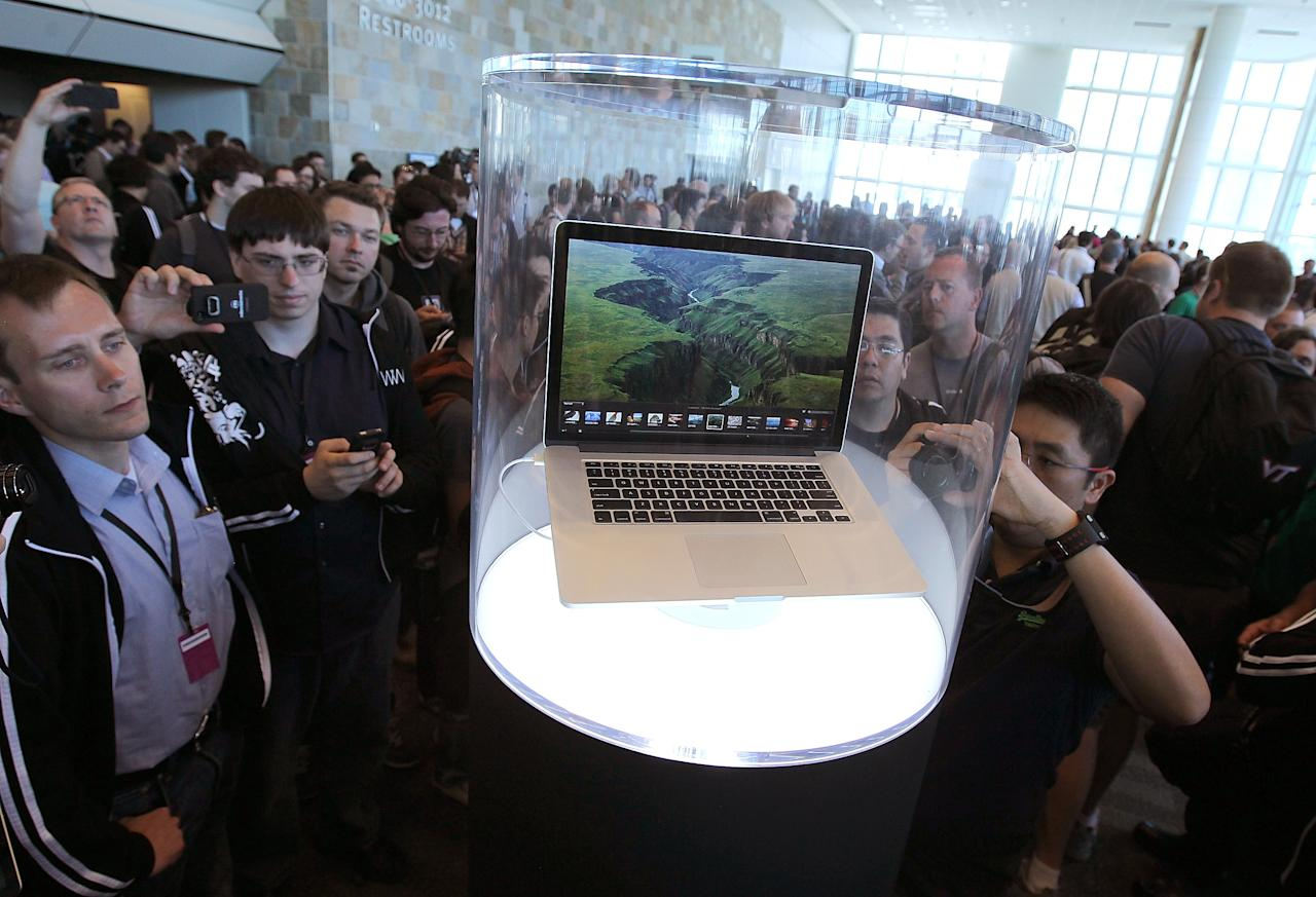 WWDC attendees look at the new MacBook Pro that is displayed at the 2012 Apple WWDC keynote address at the Moscone Center on June 11, 2012 in San Francisco, California.  Apple announced a new version of its popular Macbook Pro laptop as well as the new Mountain Lion operating system and iOS 6 for the iPhone with new features like maps. WWDC starts today and runs through  June 15.  (Photo by Justin Sullivan/Getty Images)