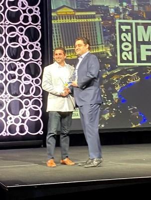 Eric Simon, Vice President Sales & Development at The Joint Chiropractic, accepts the 2021 Top$core Award from FRANdata at the Multi-Unit Franchising Conference.