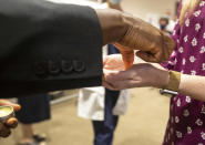 Father Don Ajoko, Phd. anoints the hands of healthcare workers and members of the nearly three dozen healthcare workers from around the country to help supplement the staff at Our Lady of the Lake Regional Medical Center in Baton Rouge, La., Monday, Aug. 2, 2021. Louisiana has one of the lowest coronavirus vaccination rates in the nation and is seeing one of the country's worst COVID-19 spikes. (AP Photo/Ted Jackson)
