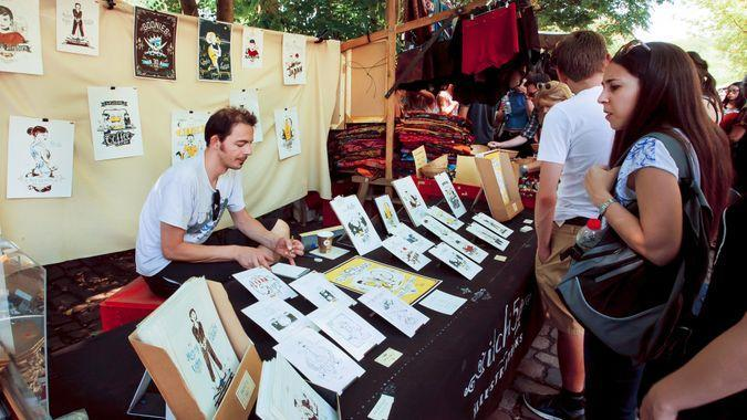 BERLIN, GERMANY - AUG 30, 2015: Young artist draws and sells graphic arts on street market in Mauerpark on August 30, 2015.