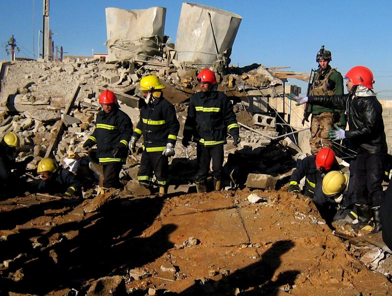 Fire fighters look for survivors at the local headquarters of the Kurdistan Democratic Party after a bomb attack in Kirkuk, 180 miles (290 kilometers) north of Baghdad, Iraq, Wednesday, Jan. 16, 2013. Two car bombs exploded in Kirkuk, the deadliest of the two explosions struck the local headquarters of the Kurdistan Democratic Party. The KDP is led by Massoud Barzani, the president of Iraq's largely autonomous Kurdish region, who has frequently sparred with Iraq's central governor in Baghdad, killing and wounding scores of people, police said. (AP Photo/ Emad Matti)