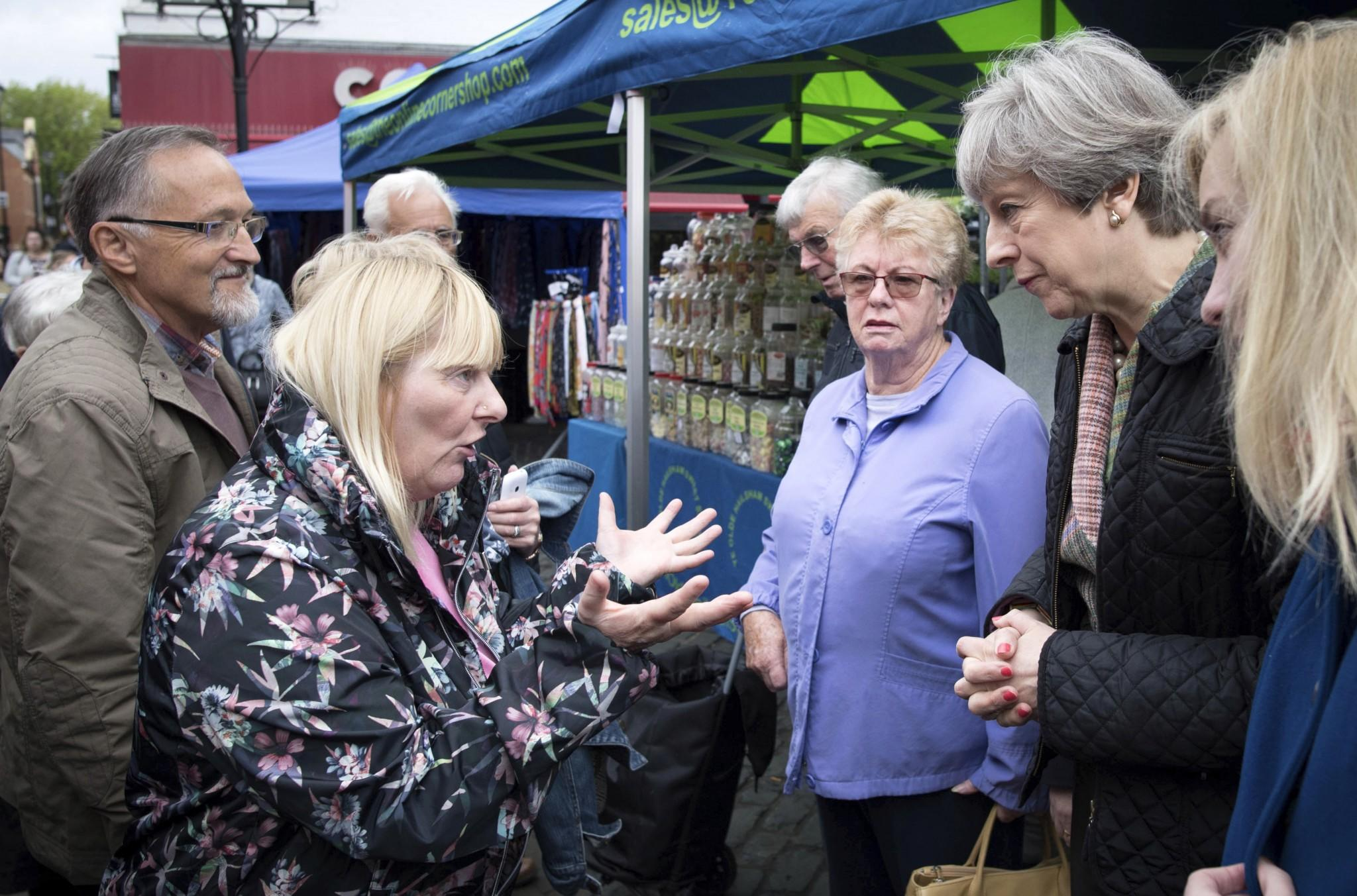 Theresa May is confronted by an angry voter (Reuters)