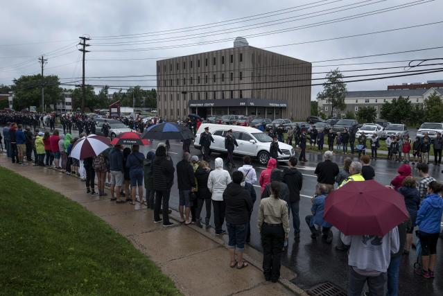 <p>The hearses carrying two slain Fredericton Police officers Const. Sara Burns and Const. Robb Costello move slowly past residents of Fredericton during a regimental funeral on Saturday, August 18, 2018. (Photo from The Canadian Press/Darren Calabrese) </p>