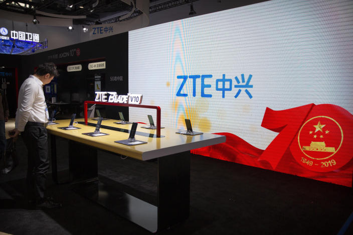 FILE - In this Thursday, Oct. 31, 2019, file photo, a man looks at products from Chinese technology firm ZTE near a screen showing a display commemorating the 70th anniversary of the founding of China at the PT Expo in Beijing. The Senate has passed a bill that provides $1 billion for small telecom providers to replace equipment in their networks that's made by China's Huawei and ZTE. It now goes to President Donald Trump. Huawei and ZTE did not immediately reply to a request for comment, Thursday, Feb. 27, 2020. (AP Photo/Mark Schiefelbein, File)