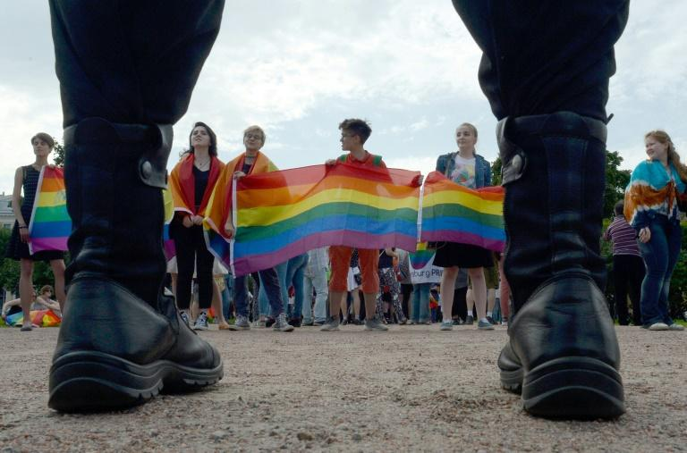 Activists wave rainbow flags at a gay pride rally in Saint  Petersburg in Agust 2017