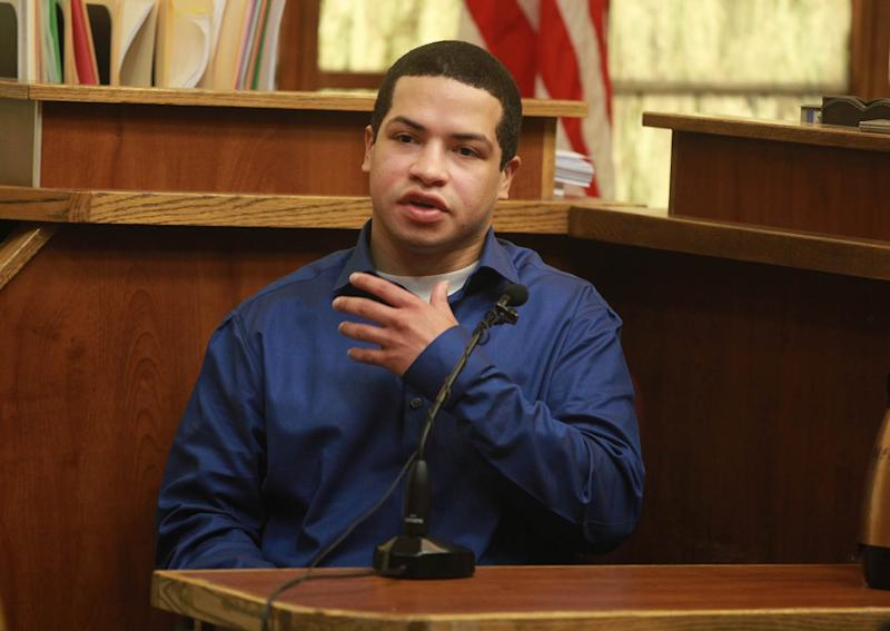 FILE - In this Oct. 29, 2013, file photo, Eric Rivera, Jr., talks with his the defense team during his trial for the slaying of Sean Taylor in MIami. Rivera was convicted Monday, Nov. 4, 2013, of second-degree murder in the 2007 killing of Washington Redskins star Sean Taylor during a botched home burglary. The jury reached its verdict after deliberating about 16 hours over several days in the case of Eric Rivera Jr. Rivera was also convicted of armed burglary. (AP Photo/The Miami Herald, Peter Andrew Bosch, Pool, File) NO SALES