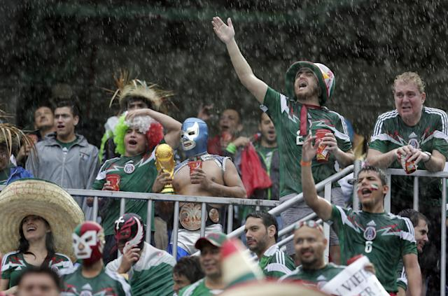 Mexican fans cheer in a downpour before the group A World Cup soccer match between Mexico and Cameroon in the Arena das Dunas in Natal, Brazil, Friday, June 13, 2014. (AP Photo/Petr David Josek)