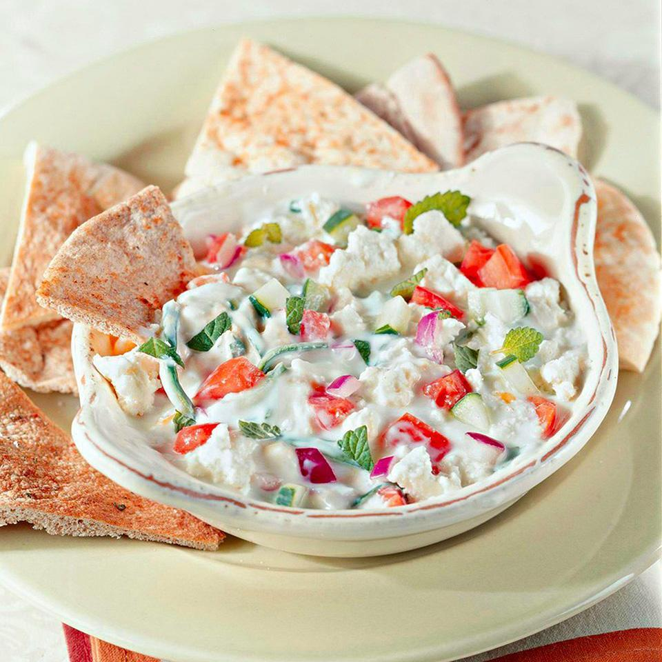 <p>The perfect dip for your next party! Cucumber, onion, and mint are mixed with low-fat yogurt, layered with hummus, tomatoes, and feta cheese, and then served with pita wedges in this Greek-inspired dip.</p>