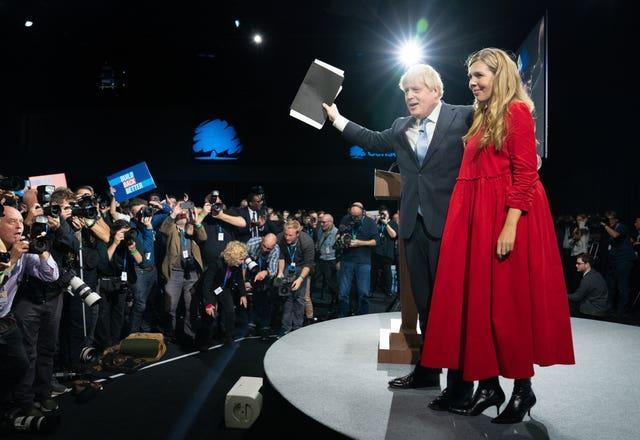 Prime Minister Boris Johnson is joined by his wife Carrie on stage after delivering his keynote speech at the Conservative Party conference in Manchester