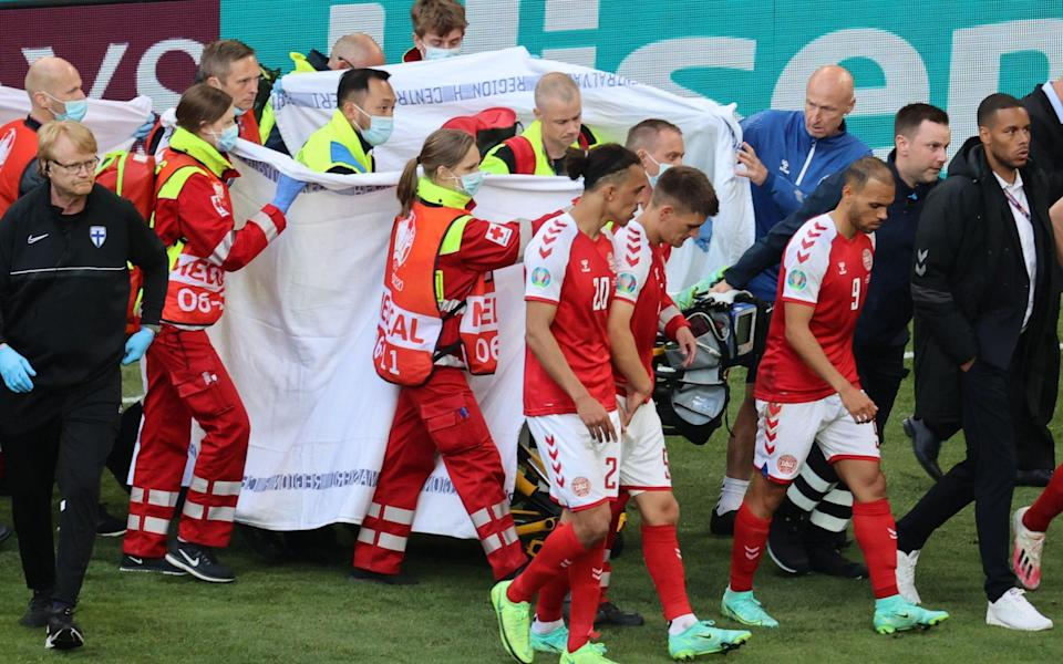 Eriksen is taken off and is shielded from view - AFP