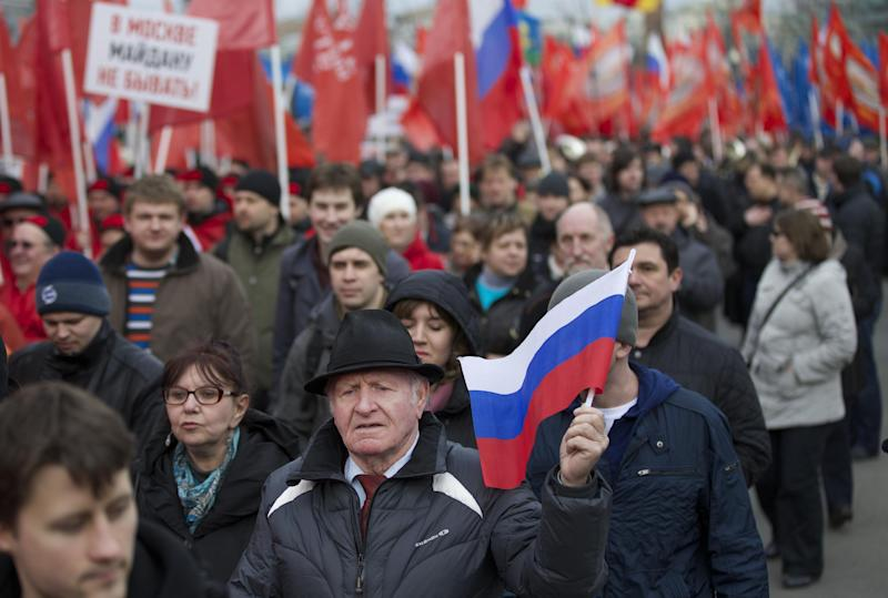 """Demonstrators march in support of Kremlin-backed plans for the Ukrainian province of Crimea to break away and merge with Russia, in Moscow, Saturday, March 15, 2014. Large rival marches have taken place in Moscow over Kremlin-backed plans for Ukraine's province of Crimea to break away and merge with Russia. The marchers belong to a group calling itself the """"Essence of Time,"""" which professes to campaign for the interests of social progress in Russia and protect the interests of Russians. (AP Photo/Alexander Zemlianichenko)"""