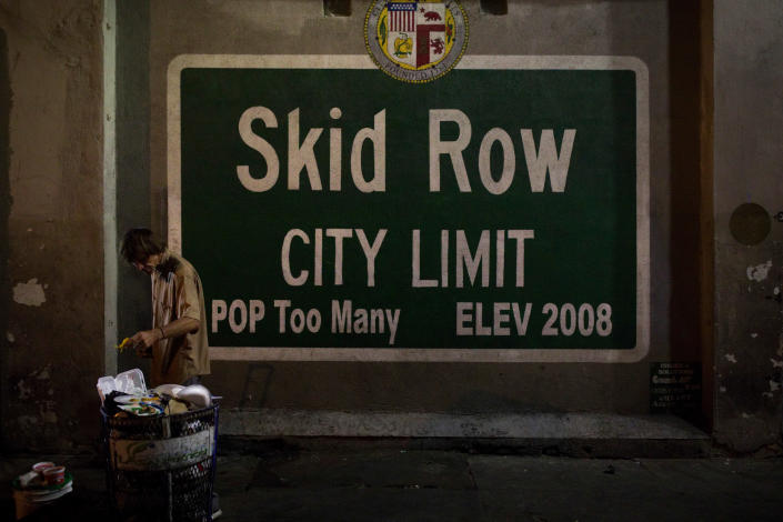 """FILE - In this Oct. 28, 2017, file photo, a homeless man takes food from a trash can in Los Angeles' Skid Row area, home to the nation's largest concentration of homeless people in Los Angeles. A fed-up federal judge says last week's rainstorm created """"extraordinarily harsh"""" conditions for homeless residents of Los Angeles and he has ordered city officials to meet with him this week at a Skid Row shelter to discuss how to address the worsening crisis of people living on the streets. (AP Photo/Jae C. Hong, File)"""
