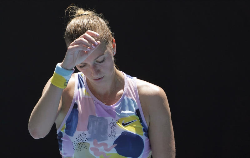 Petra Kvitova of the Czech Republic wipes the sweat from her face during her quarterfinal match against Australia's Ashleigh Barty at the Australian Open tennis championship in Melbourne, Australia, Tuesday, Jan. 28, 2020. (AP Photo/Lee Jin-man)