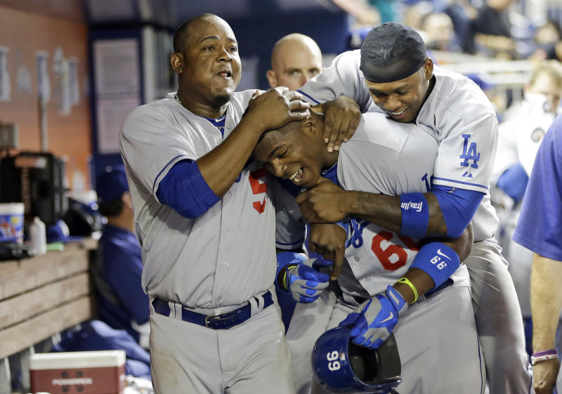 Los Angeles Dodgers' Yasiel Puig, center, is congratulated in the dugout by teammates Juan Uribe, left, and Hanley Ramirez, right, after hitting a home run in the eighth inning during a baseball game against the Miami Marlins, Tuesday, Aug. 20, 2013 in Miami. The Dodgers won 6-4.(AP Photo/Lynne Sladky)